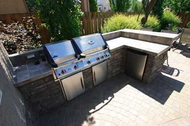 backyard kitchen featuring grill and fridge and bar