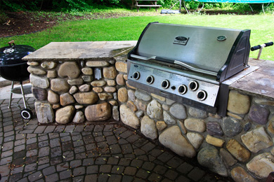 Outdoor kitchen with gas grill in fieldstone base