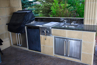 Outdoor kitchen with stone countertops, fridge, BBQ grill and more