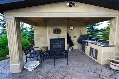 This outdoor living space is a poolhouse with change rooms, outdoor kitchen and outdoor fireplace