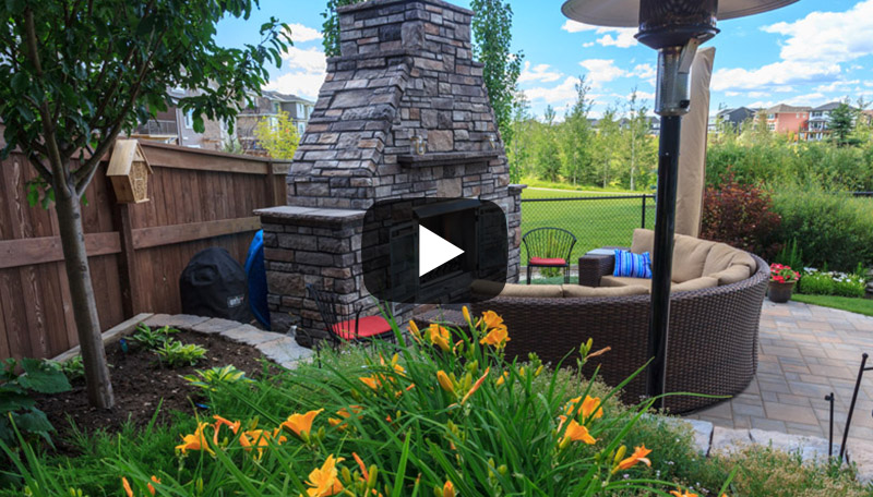 View this Auburn Bay sloped yard with landscaping features such as retaining walls, outdoor fireplace structure and a bubblerock water feature